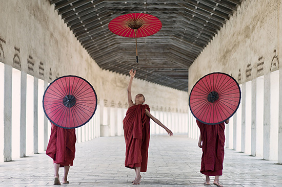 ICNL 2012-2013 Annual Report cover photo - A group of three monks with red umbrellas