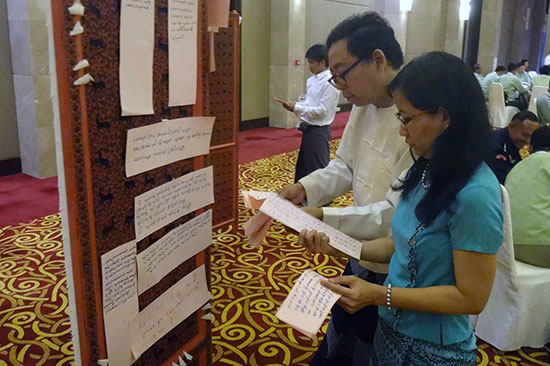 Participants reading over a poster at a July, 2016 workshop in Myanmar on the implementation of the Association Registration Law, convened by the CSO Working Group and the Ministry of Home Affairs, with the support of USAID and FHI 360.