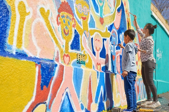 ICNL 2018-2019 Annual Report cover photo - mother and son paint a vibrant mural. (Photo: Caiaimage/Trevor Adeiline)