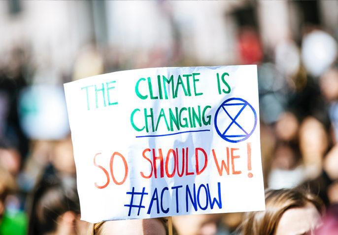 Person holding climate change sign with Extinction Rebellion symbol. (Photo: Markus Spiske/Unsplash)