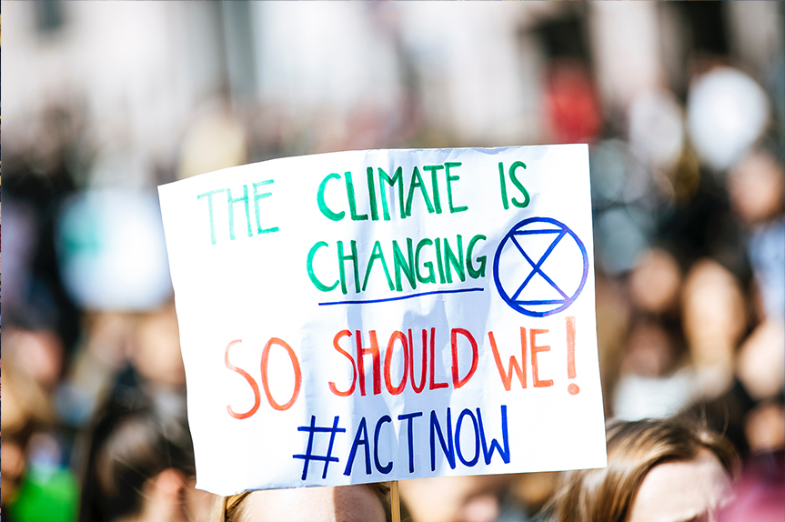 Person holding climate change sign with Extinction Rebellion symbol. (Photo: Markus Spiske/Unsplash)