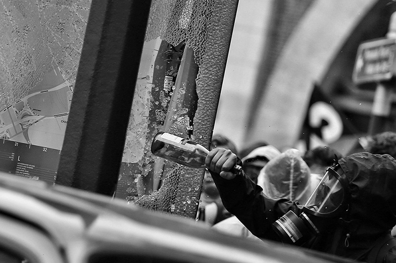 Protester smashing a window with a bottle (Photo credit: Randy Colas/Unsplash)