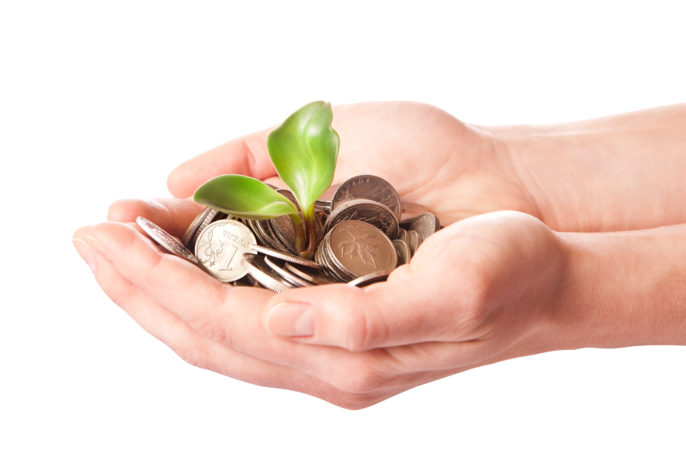 Hands holding money with a seedling growing - symbolizes a new investment (Photo: 401(K) 2012/Wikipedia)