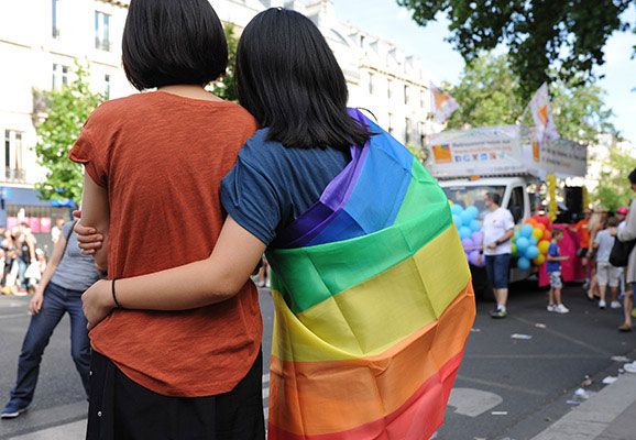 A couple watches a Pride Parade, while wrapped in a rainbow flag (photo credit: Wikimedia Commons)