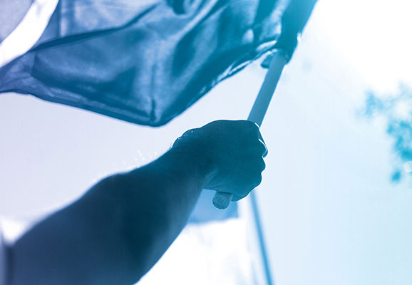 A man hoists a flag into the air (photo credit: Artem Nezvigin/Flickr)