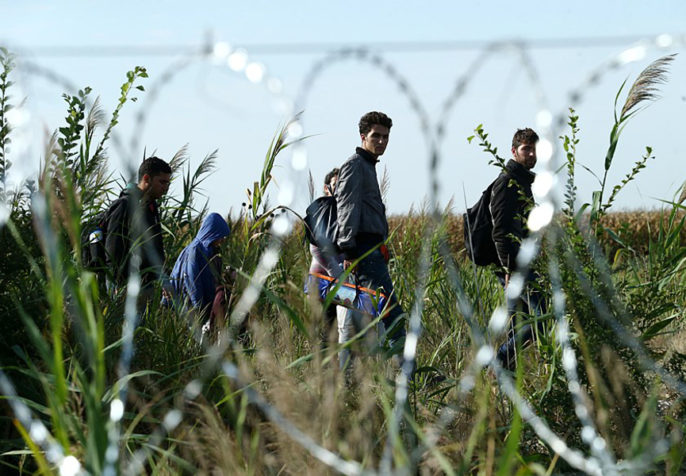 Migrants in hungary with barb wire fence (photo credit: Gémes Sándor/SzomSzed/Wikimedia)