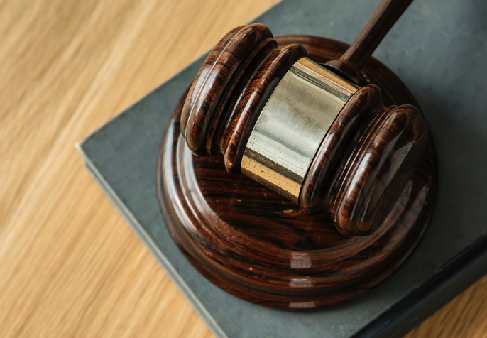 Judges gavel laying on wood table (Photo credit: Rawpixel/Unsplash)