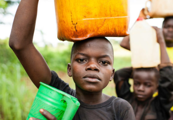 Donatien Voungoukpala, 13 (solid blue t-shirt), with his brothers Fleuri Rodrigue Hipai, 17, and Aime Bera-Mbolikia, 10, go to fetch water at a a nearby spring, their principle water source. August 20, 2012, Rounga Village, Bangassou, Central African Republic. Donatien and his family are IDPs who relocated to Bangassou from Rafai approximately one year ago as a result of the LRA conflict.