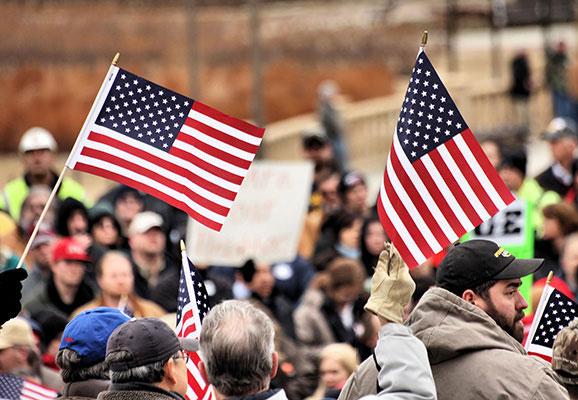 Workers hold US flags at a labor rally in Iowa (photo credit: Phil Roeder/Flickr)