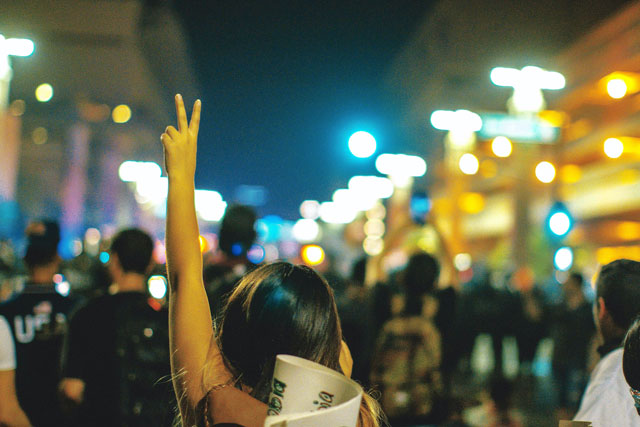 Women giving peace sign at protest (photo credit: unsplash.com)