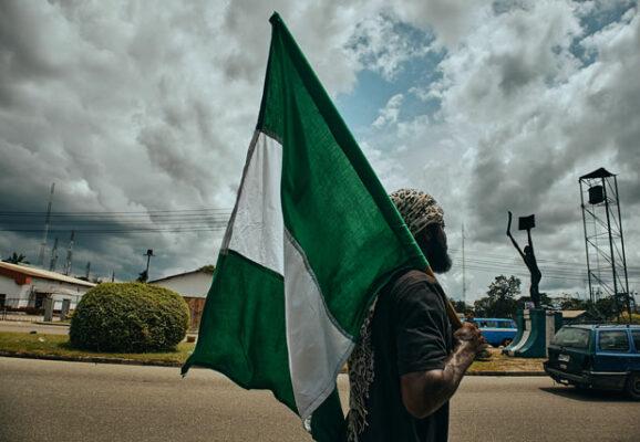nigeria protester with flag (credit: unsplash.com)