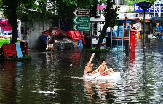 two boys on canoe in flood waters (photo credit: