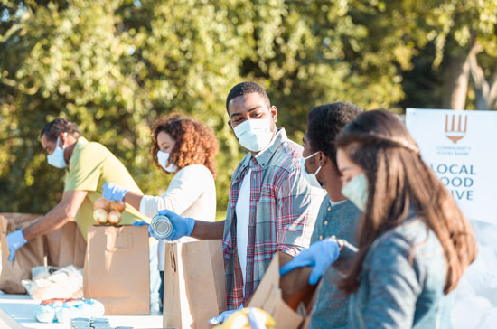 Group of people wearing masks, sorting food in bags for a food drive (Photo: istock)