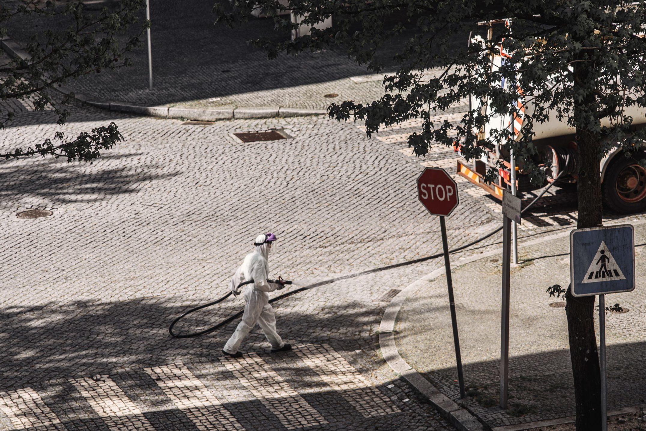 man in hazmat suit cleaning streets (photo credit: unsplash.com)