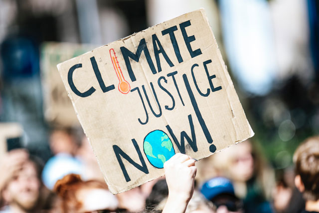 Cardboard sign at protest that says Climate Justice Now (photo credit: unsplash.com)