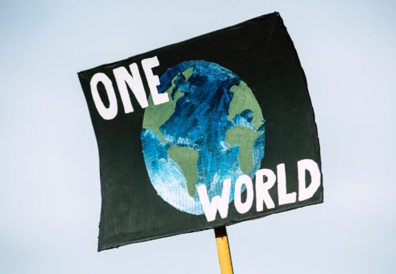 sign that says one world with Earth (photo credit: unsplash.com)