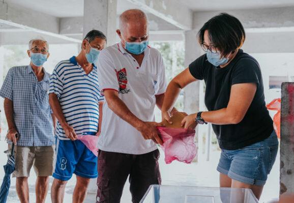 women giving food to men in line (photo credit: unsplash.om)