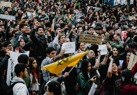 protestors in Chile with signs and flags (photo credit: unsplahs.com)