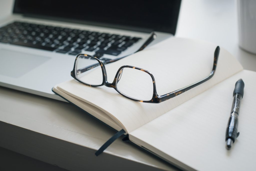 glasses on book with computer (photo credit: unsplash.com)